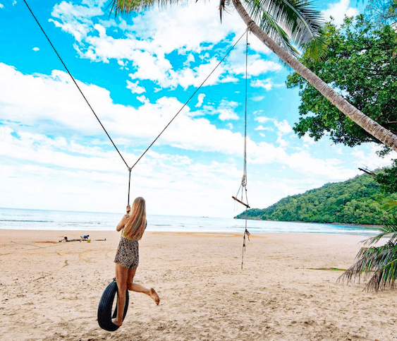 Woman on tree swing at the beach