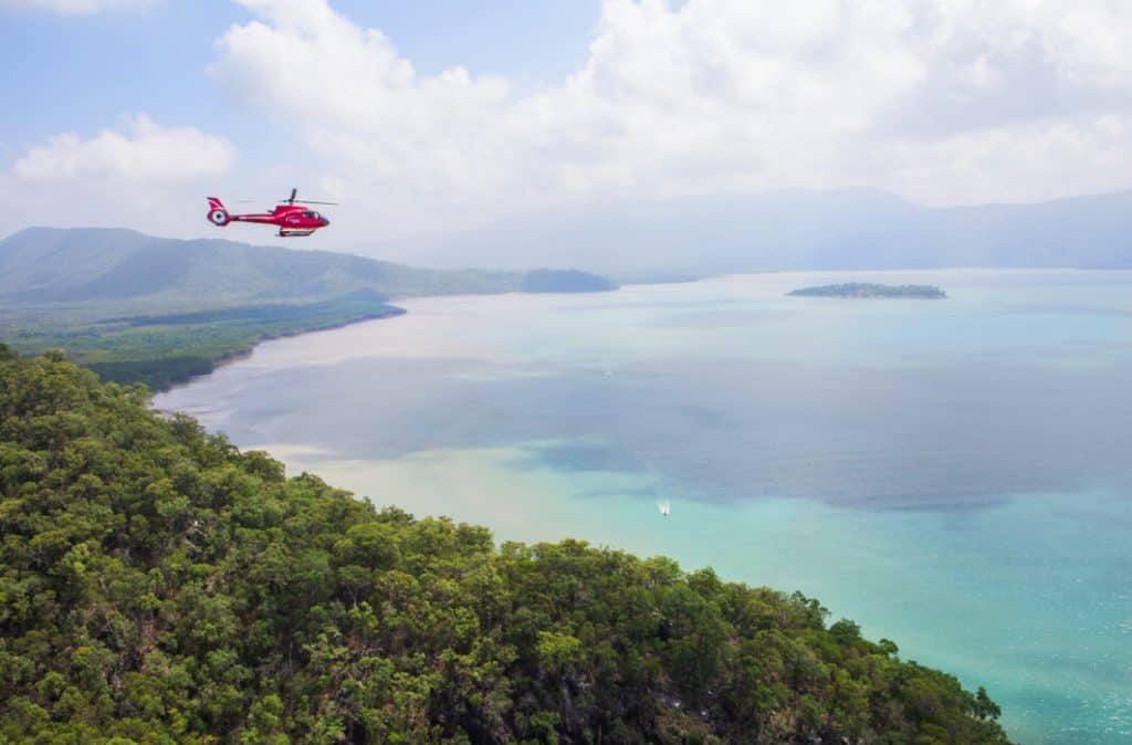 Nautilus Aviation helicopter flying out from rainforest to ocean