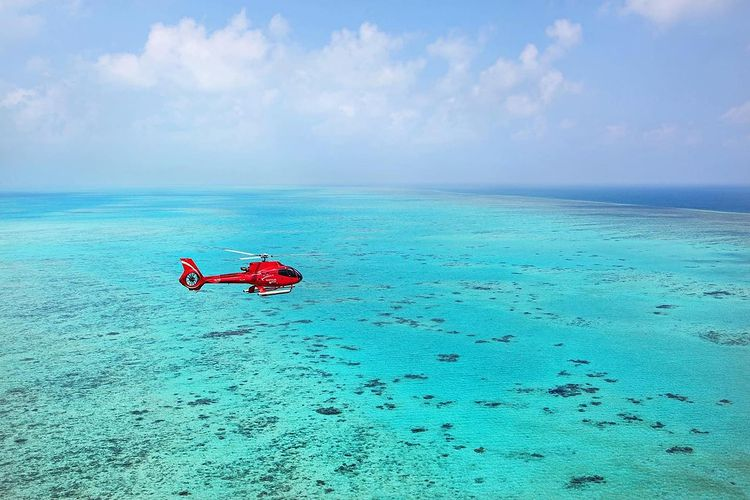 Nautilus Aviation red helicopter flying across Great Barrier Reef near Port Douglas