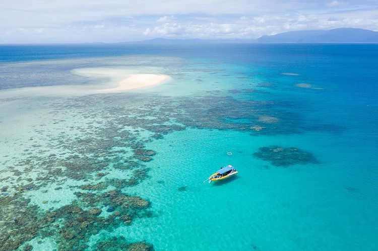 Aerial shot of sand cay surrounded by blue ocean