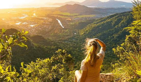 Girl sitting overlooking rainforest at sunrise
