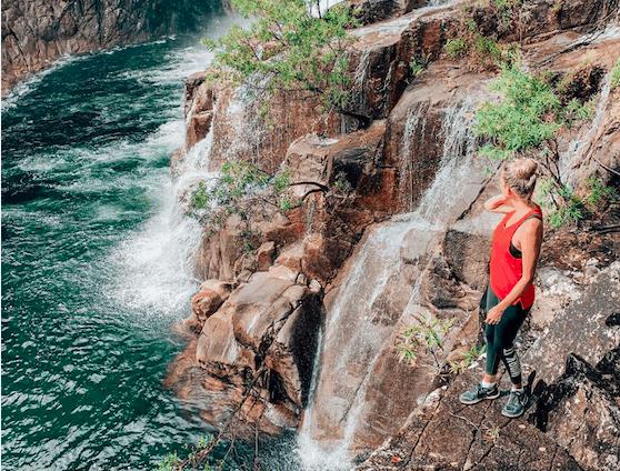 Girl standing on rocks near waterfall